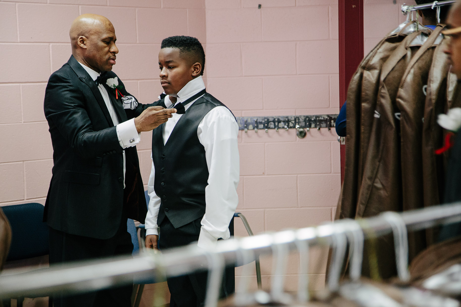 A young man gets help putting on his bowtie for the 500 Black Tuxedos Event, organized by Andre Lee Ellis, on Saturday December 12th, 2015 in Milwaukee, Wisconsin.