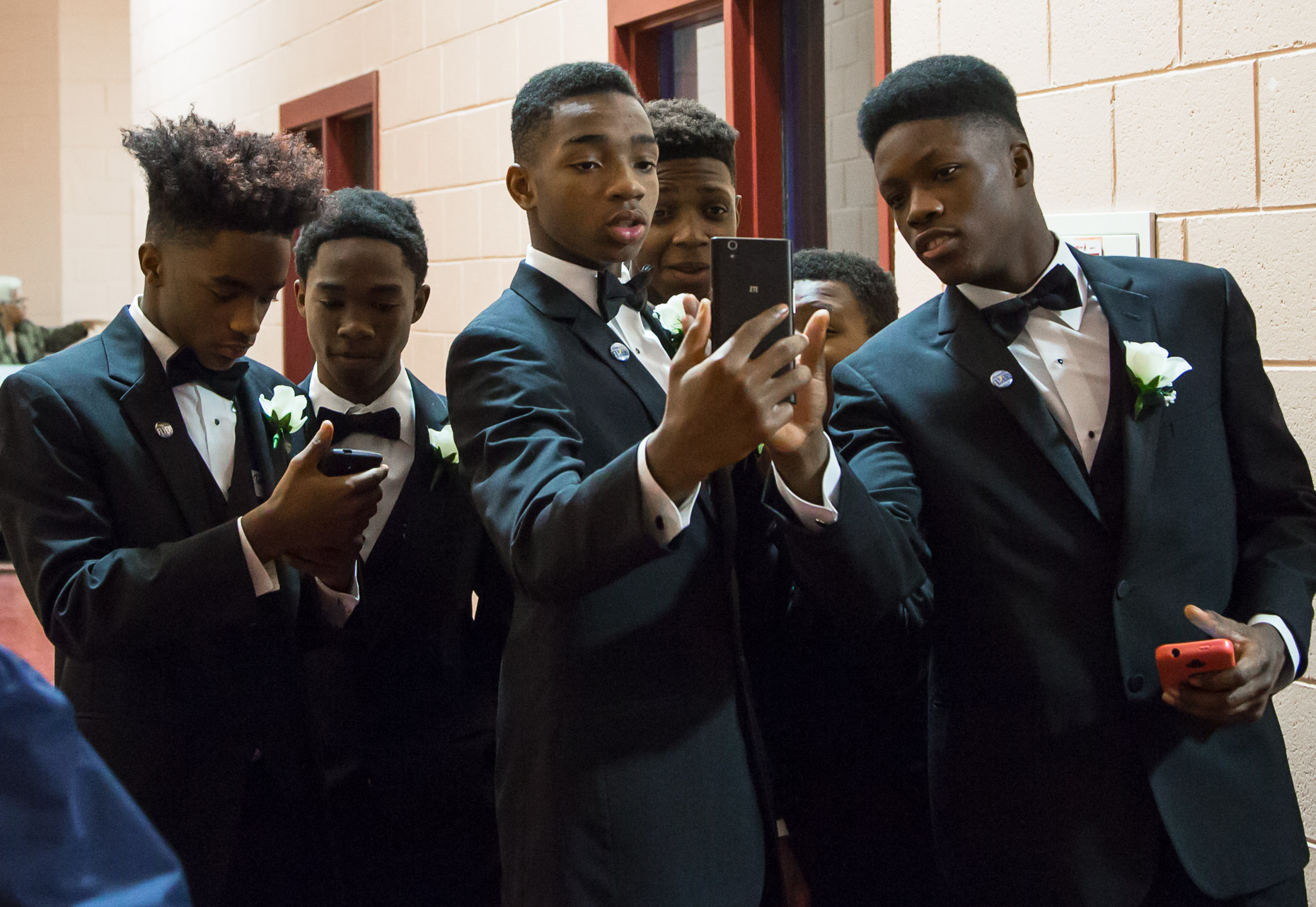 A group of young men pose for a group selfie at the Northcott Neighborhood House for the 500 Black Tuxedos Event, organized by Andre Lee Ellis on Saturday December 12th, 2015 in Milwaukee, Wisconsin.