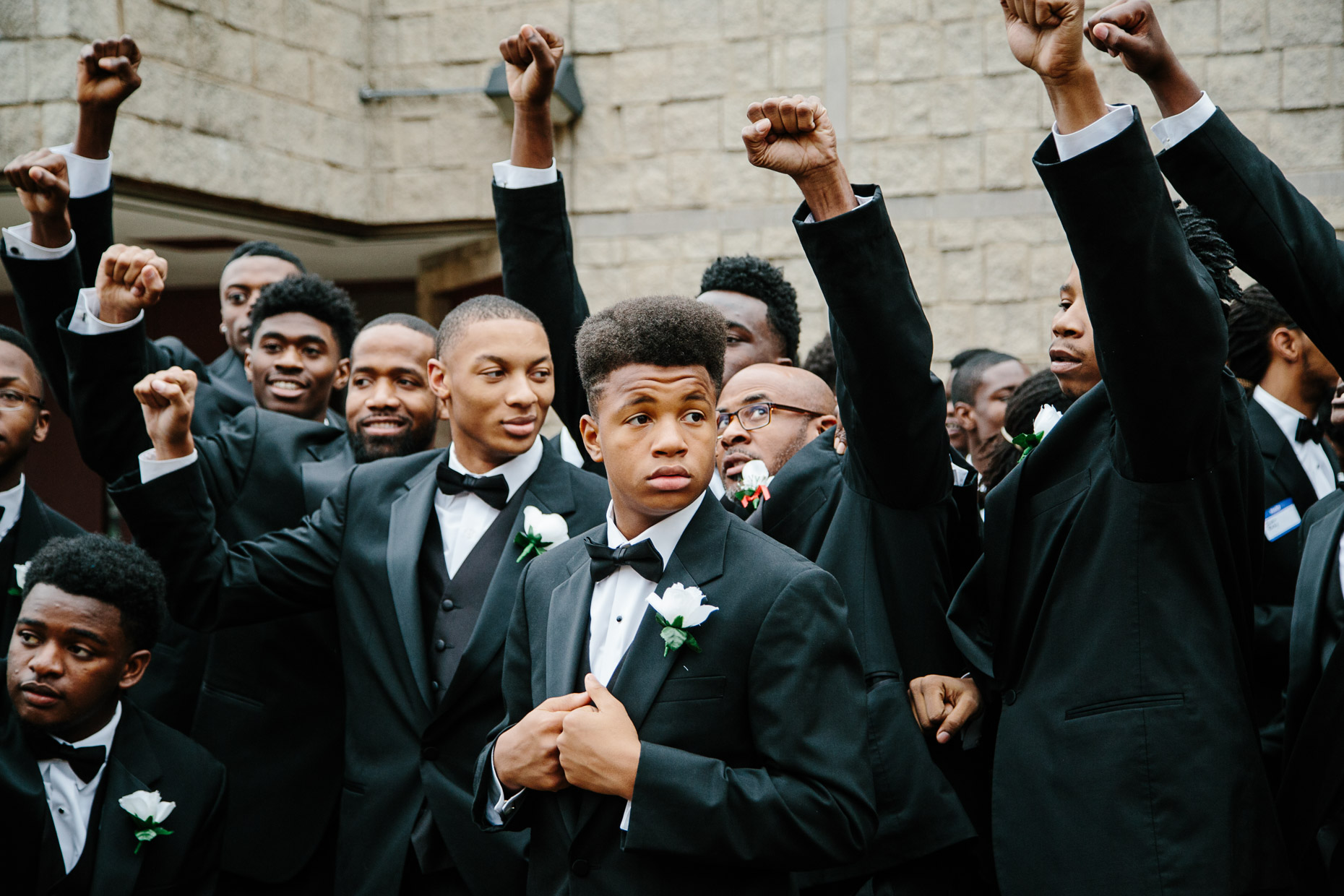 A group of young men pose for a group photo outside the Northcott Neighborhood House during the 500 Black Tuxedos Event, organized by Andre Lee Ellis on Saturday December 12th, 2015 in Milwaukee, Wisconsin.