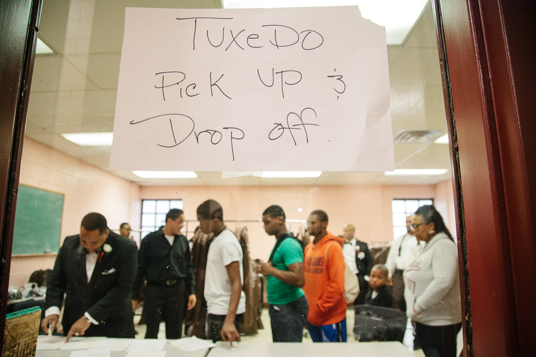 A group of young men line up to pick up their tuxedos in a room at the Northcott Neighborhood House for the 500 Black Tuxedos Event, organized by Andre Lee Ellis, on Saturday December 12th, 2015 in Milwaukee, Wisconsin.