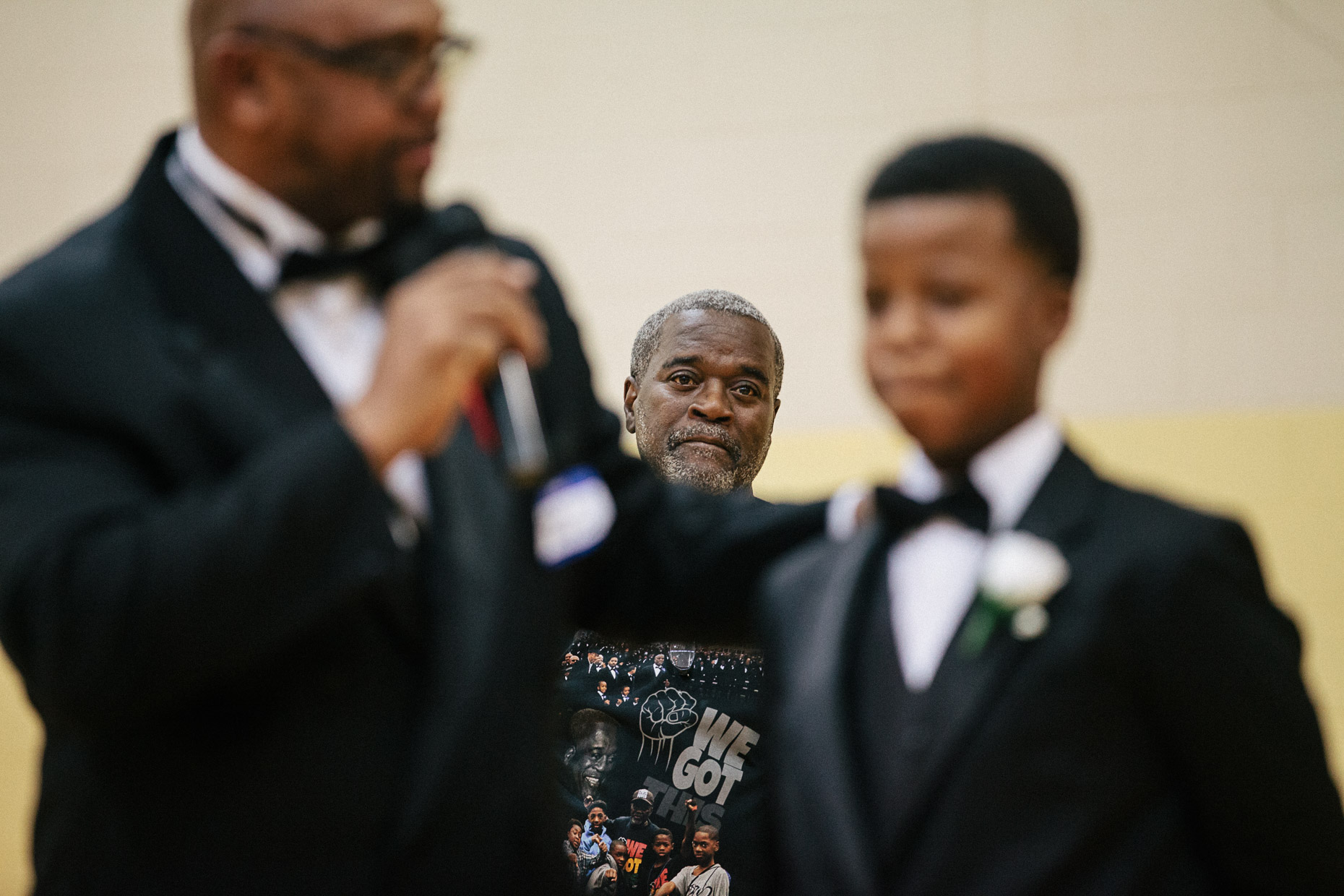 Andre Lee Ellis,  organizer of the 500 Black Tuxedos Event, listens to a speaker talk about a young man, during the group gathering in the gym of the Northcott Neighborhood House on Saturday December 12th, 2015 in Milwaukee, Wisconsin.