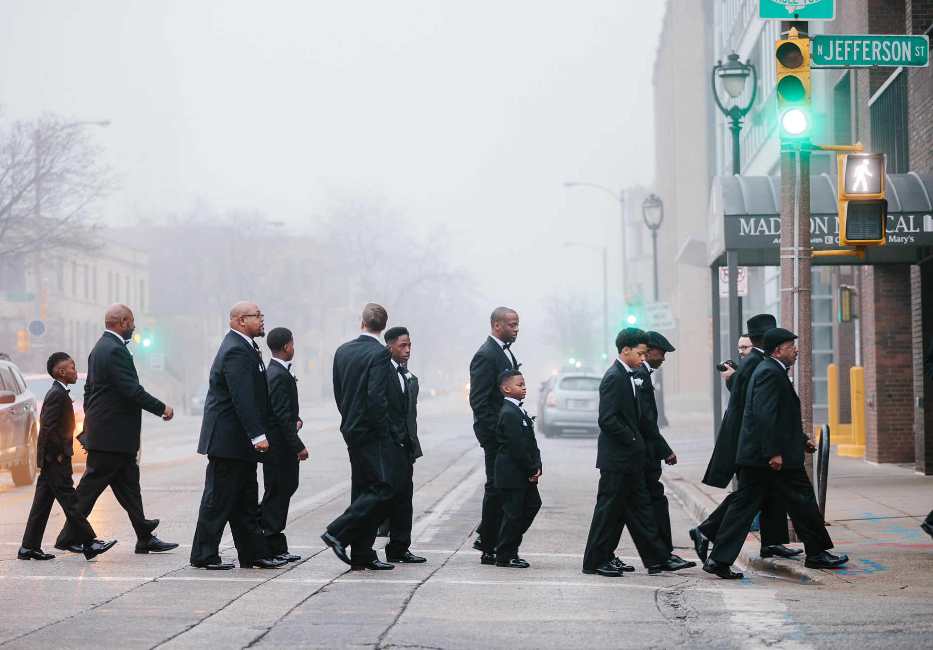 Andre Lee Ellis, the organizer of the 500 Black Tuxedos Event, leads the participants from the bus drop off point on Cathedral Square to the luncheon location at  the Chic Cafe on Jefferson Street Saturday December 12th, 2015 in Milwaukee, Wisconsin.