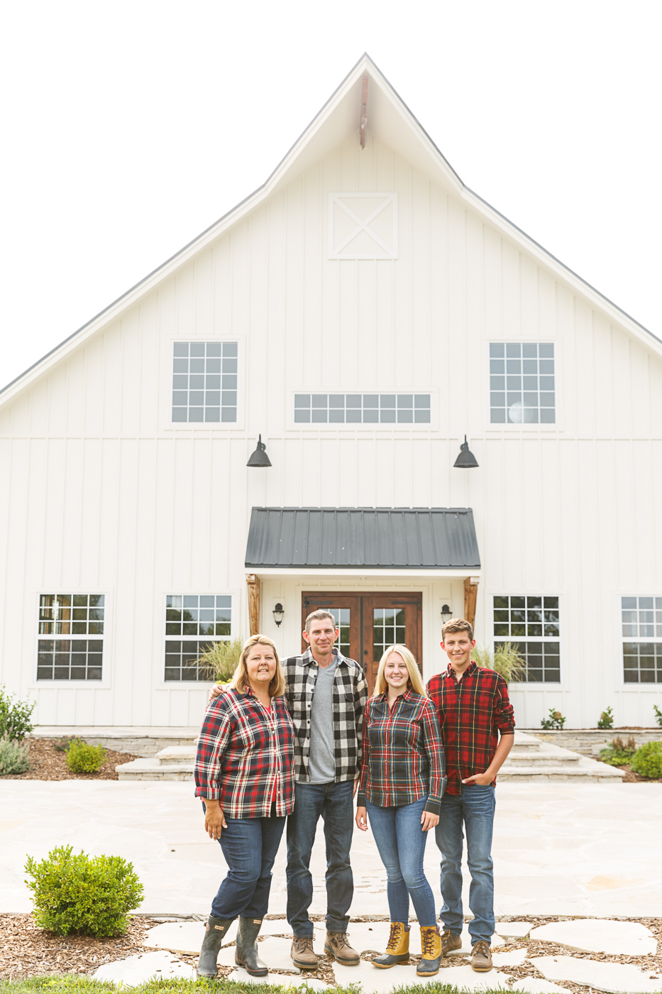 Jennifer, Joe, Abby, and Charlie Fahey (mom, dad, sister, brother) stand in front of the barn on the grounds of their organic apple orchard, Peck and Bushel, in Colgate, WI.