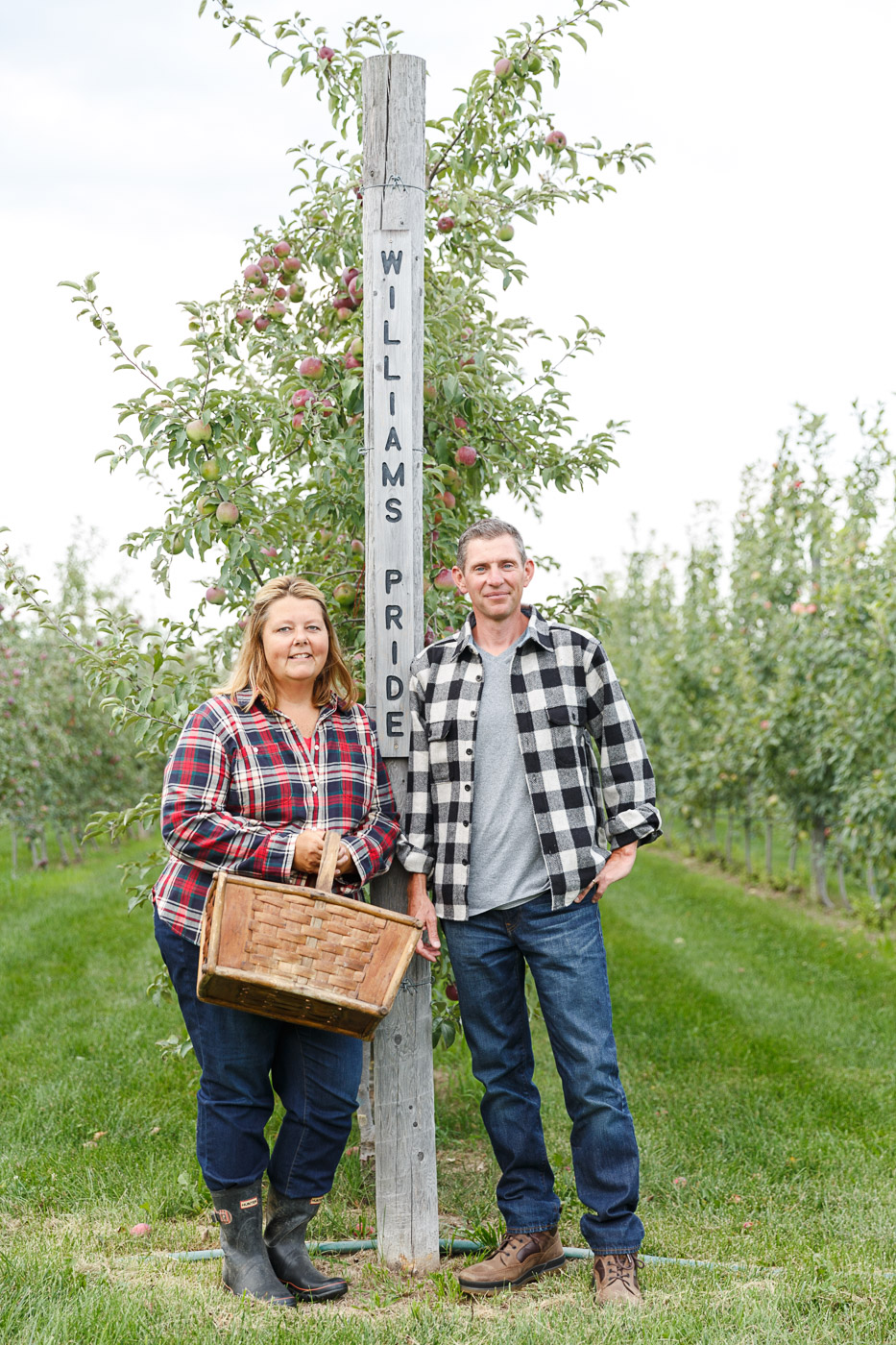 Jennifer and Joseph Fahey stand at the end of a row of trees in their Peck and Bushel organic orchard in Colgate, WI.