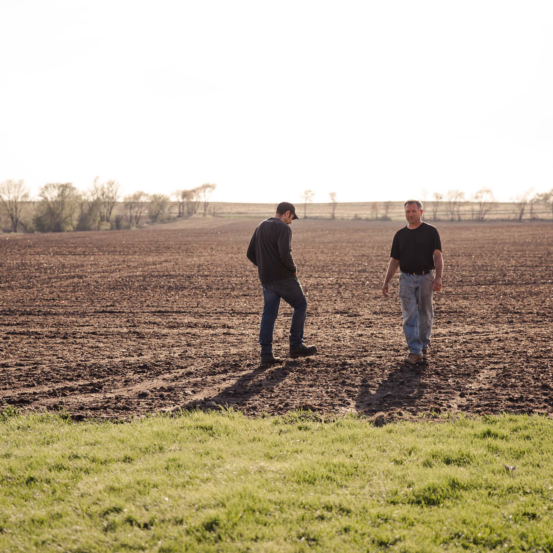 Joe Woodman and his father, Ron, walk in a freshly planted field of corn on their family farm in Janesville, Wisconsin.